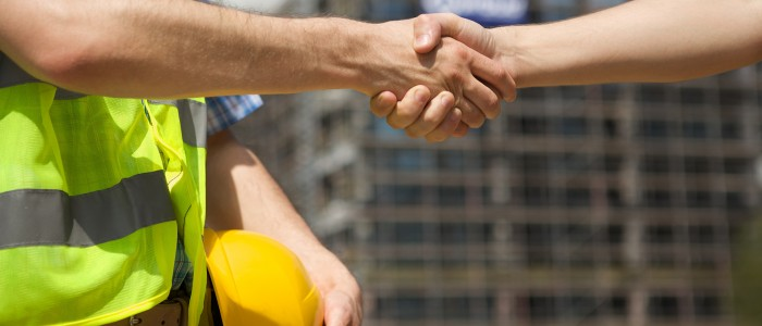 Architects shaking hand at construction site